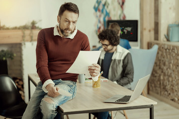 Bearded handsome businessman in jeans reading a document