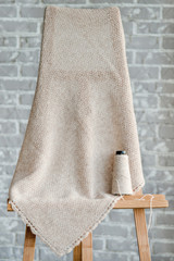 The handmade woolen cloth hangs on an easel. There is a reel of threads nearby.