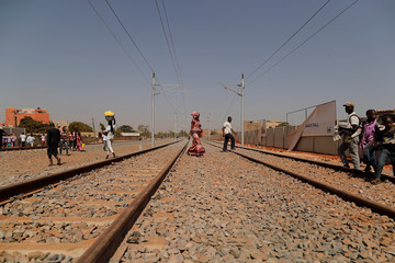 People cross newly built railway tracks of the high speed rail in Mbao, on the outskirts of Dakar