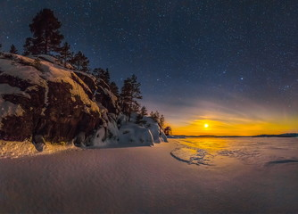 Northern lights on Lake Ladoga in the Republic of Karelia. Full moon and northern lights on the lake. Night panoramas.