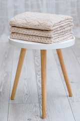 A stack of knitted handmade plaids is lying on a tabouret