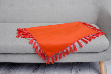 Bright orange plaid with tassels lying on the couch