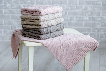 Stack of knitted plaids with patterns