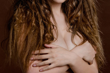 A young woman with long curly hair covers her nude breasts with her hands.
