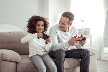 Involved father and daughter playing games together