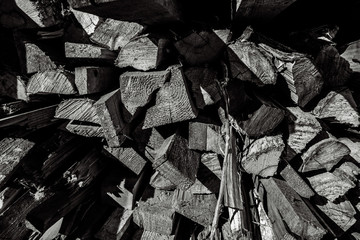 Wooden firewood stacked in a pile in firewood. Firewood in firewood