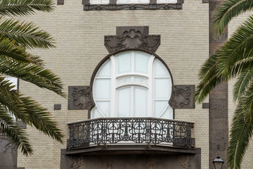 Classical style balcony on the building with palm trees