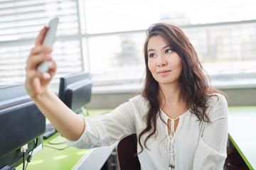 Junge Frau macht ein Selfie mit dem Smartphone