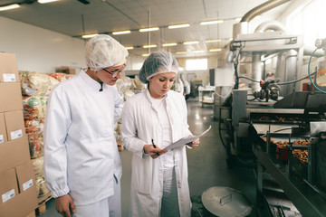 Two quality professionals in white sterile uniforms checking quality of salt sticks while standing in food factory.