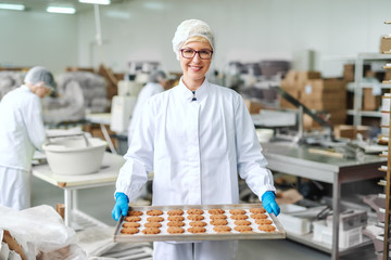 Smiling blonde Caucasian employee in sterile uniform and with eyeglasses standing and holding tray with cookies. Food factory interior. In background other employees working.