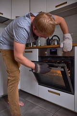 A man checking the readiness of food in the oven