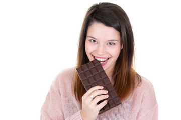 Laughing young woman in knitted pink sweater holding in hand biting and eating chocolate bar isolated on white blank wall background