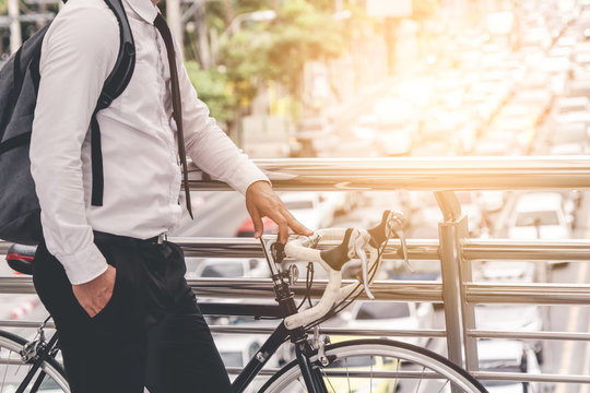 adult man on bike in the city in the morning with sun flare