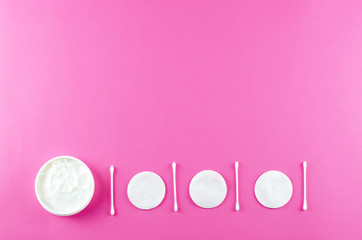 Care cosmetics and beauty accessories on a pink background.