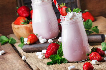 Strawberry smoothies and cocktails with fresh berry and green mint, decorated marshmallows, summer drink, wood old background, selective focus