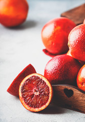 Red bloody oranges for making freshly squeezed juice, gray table background, selective focus, place for text