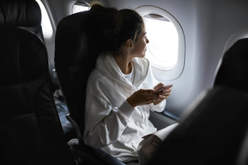 Woman with smartphone sits on black seat in plane Wall mural