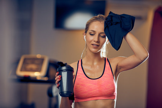 Young Caucasian smiling sporty woman in sportswear holding bottle of water and wiping sweat while standing in gym.