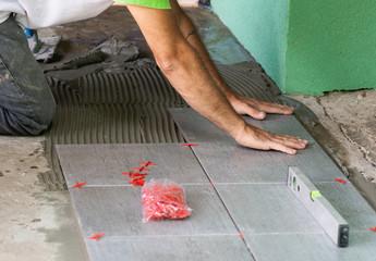 Worker installing floor tiles