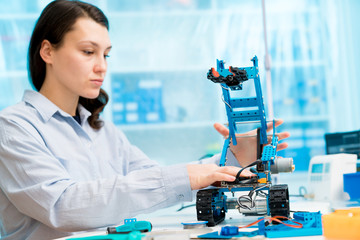 Student girl in electronics laboratory, experiment with microcontroller and robot cnc module