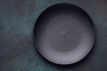 Empty black plate on dark background. Top view, with copy space