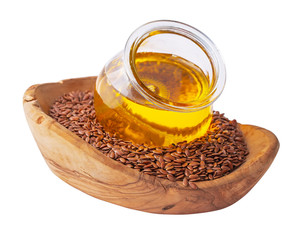 Small jar of linseed oil in wooden bowl of flax seeds