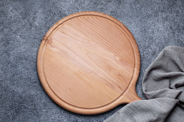 Wooden platter and napkin on gray background. Kitchen accessories for serve. Top view with copy space