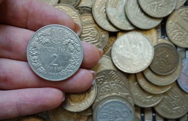 Ukrainian coins in denominations of 1 hryvnia and others, folded in a slide. Eagle and tails.