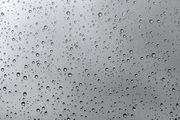 texture of rain drops on window glass over blur and cloudy sky background