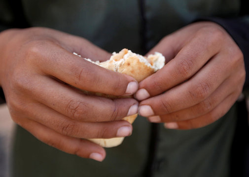 A student holds a sandwich after breakfast was distributed free of charge at a school in Sanaa