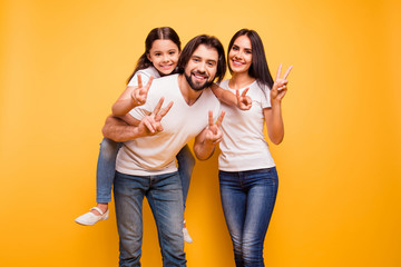 Portrait of nice cute sweet lovely attractive charming cheerful dreamy funny people mom dad pre-teen girl showing v-sign isolated over shine vivid pastel yellow background
