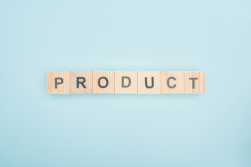 top view of product lettering made of wooden cubes on blue background