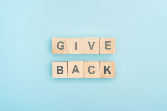 top view of give back lettering made of wooden cubes on blue background