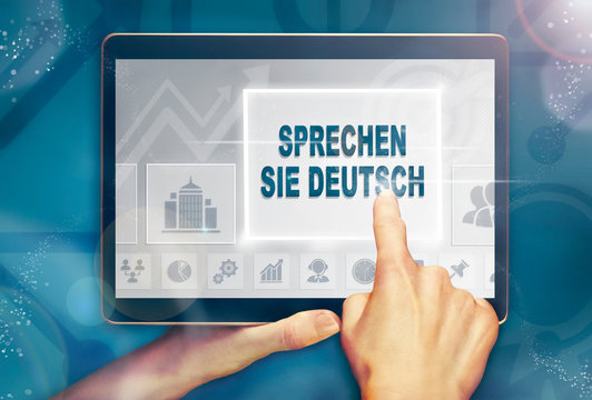 "A hand holiding a computer tablet and pressing a Do You Speak German ""Sprechen Sie Deutsch"" business concept."