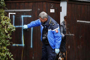 A French gendarme inspects a door that is desecrated with a swastika near the Jewish cemetery in Quatzenheim