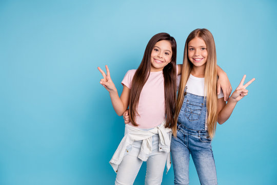 Portrait of two people nice cute lovable lovely sweet charming dreamy attractive cheerful straight-haired pre-teen girls siblings showing v-sign isolated on blue turquoise background
