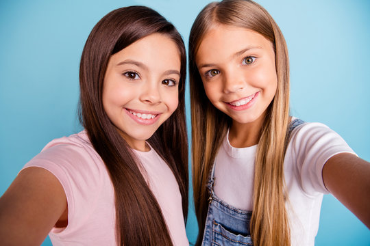Close up photo two little she her blond brunette girls long pretty hair telephone make take selfies mom mommy skype talk tell speak wearing casual jeans denim t-shirts isolated blue bright background