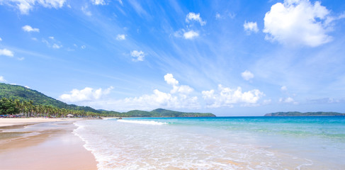 Beautiful amazing gold colored sandy beach with soft waves isolated with sunny blue sky. Concept of tropical calm tourism idea, copy space, close up