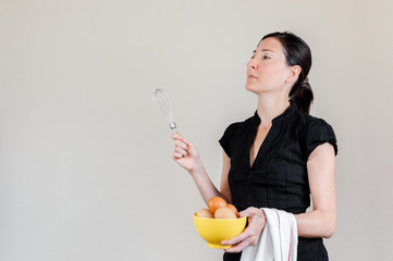 Beautiful Caucasian woman with black shirt holding an eggbeater and a yellow bowl full of chicken eggs