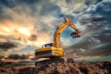 Crawler excavator during earthmoving works on construction site at sunset