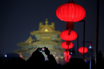 Visitor takes a picture of the Forbidden City decorated with red lanterns that is lit up during an event to celebrate the Chinese Lantern Festival on the last day of the lunar new year celebrations in Beijing