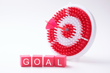 Meeting goal concept with red dart arrow hitting the center of dartboard