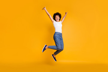 Full length body size side profile photo jumping high beautiful she her lady hands arms up win game play match wearing casual jeans denim white t-shirt clothes isolated yellow bright vivid background