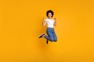 Full length body size side profile photo jumping high beautiful she her lady yelling loud voice hands arms up win wearing casual jeans denim white t-shirt clothes isolated yellow bright background