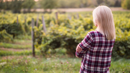 Young woman farmer looks at his garden or vineyard