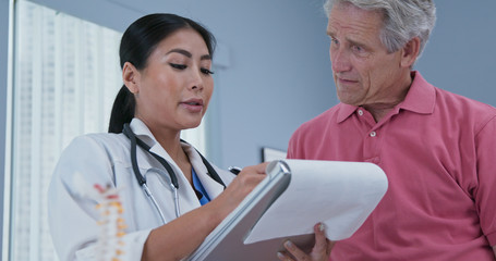 Low-angle view of Japanese woman primary care doctor talking to senior Caucasian male patient. Physician having conversation with aging man in her medical office