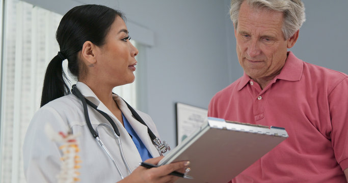 Female primary care physician taking medical history from senior Caucasian male patient. Japanese woman doctor talking to aging man and making notes