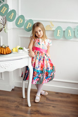 Full length of a little smiling girl in colorful dress posing in a decorated room for the holiday Easter is waiting for an Easter lunch