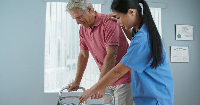 Senior Caucasian male patient learning to use walker with the assistance of Asian female physical therapist or nurse. Doctor helping older man walk again in recovery
