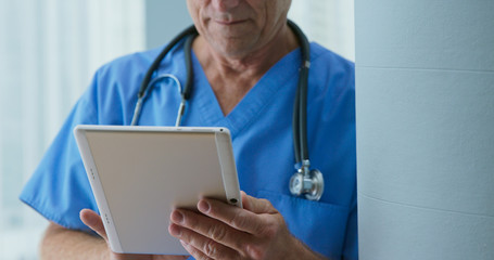 Close up on tablet computer to Senior Caucasian male doctor as he reads medical history of patient. Older man medical professional looking over records on pad